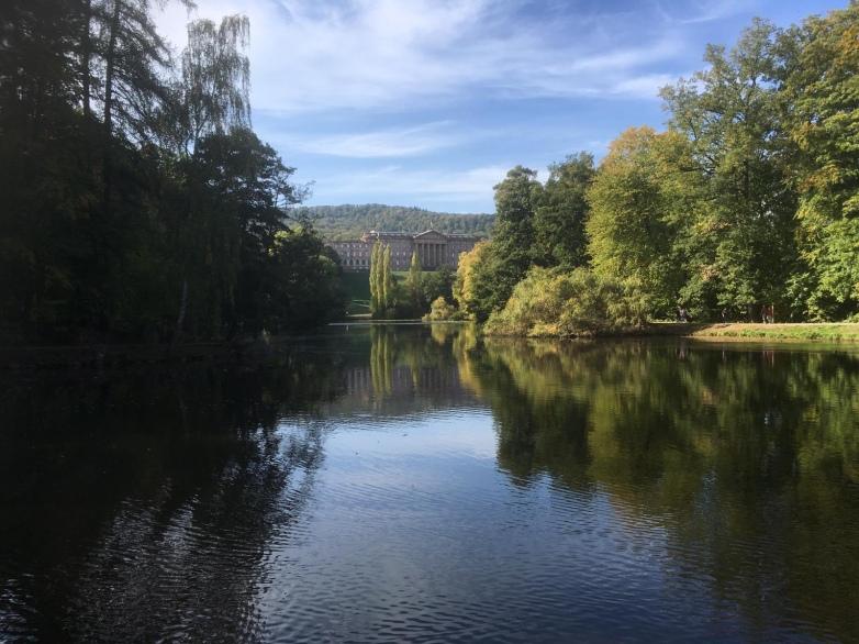Von der Sonne beschienene Bäume und ein Schloss im Hintergrund spiegeln sich im See.