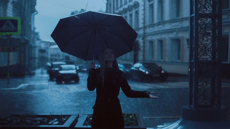 Frau hält einen Regenschirm und die andere Hand im Regen.