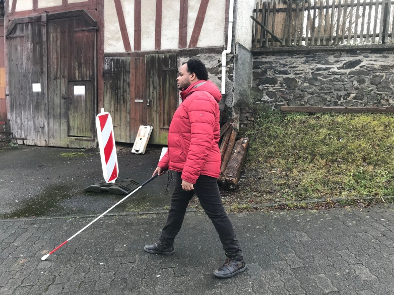 Mann, Der mit Blindenstock an einer Straße entlang läuft