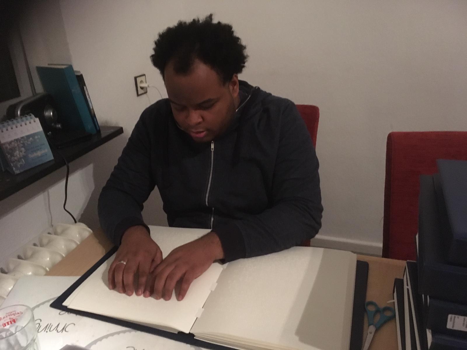 Arbeiten im Homeoffice:Johannes liest in der Blindenschrift-Bibel