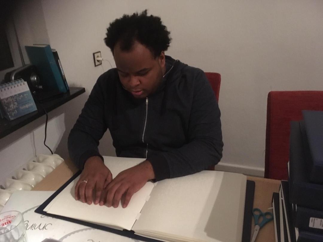 Mann, der mit Fingern in einem Blindenschriftbuch liest.