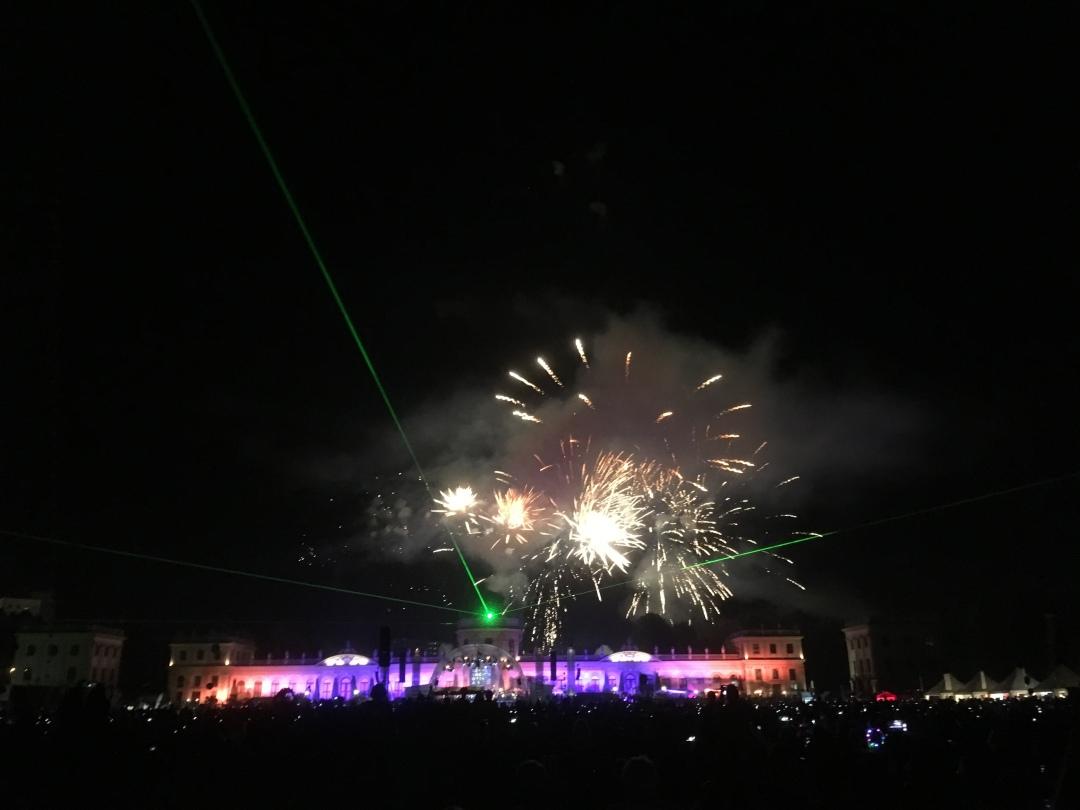 Feuerwerk hinter der lila-orange beleuchteten Orangerie