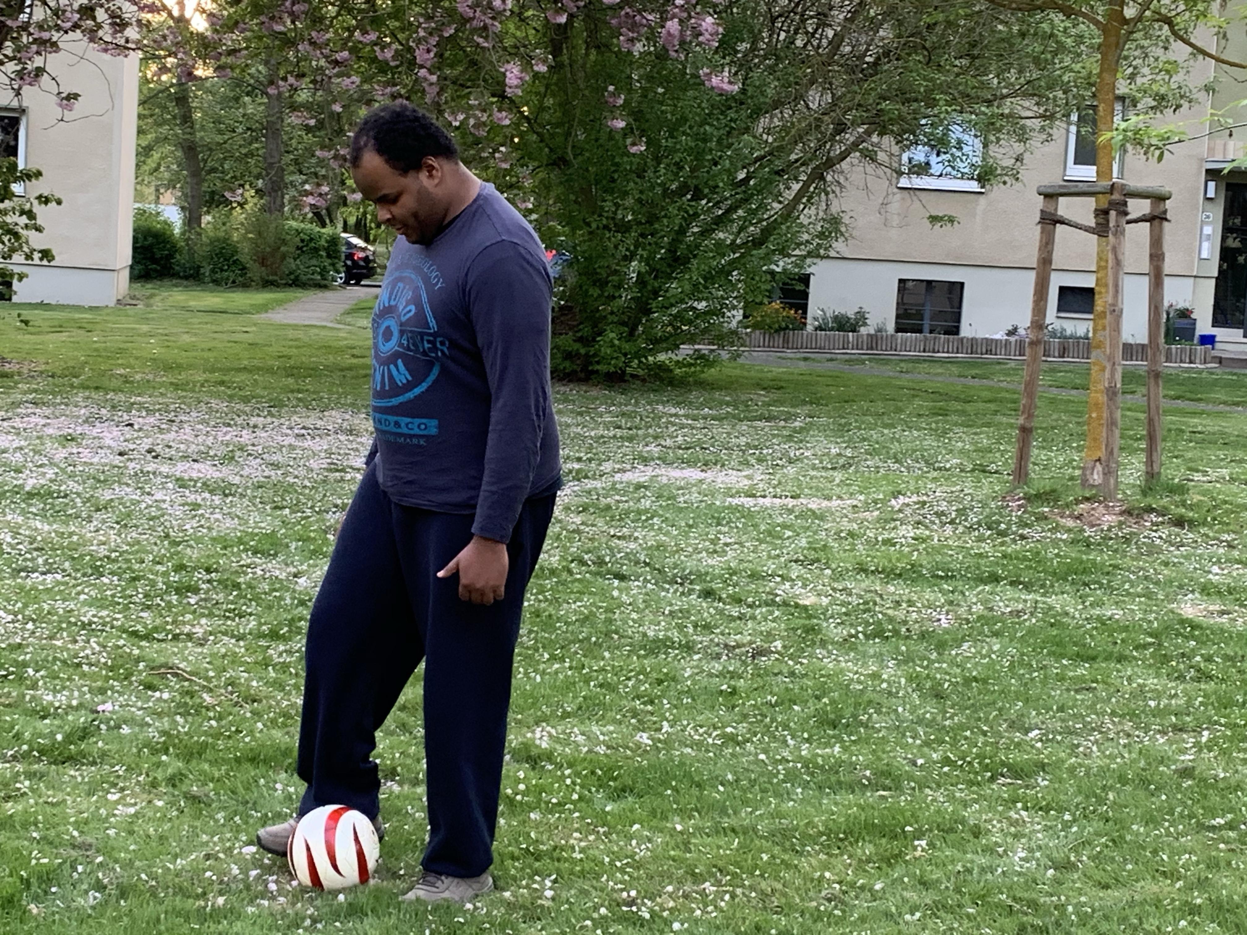 Johannes trippelt mit dem Blindenfußball auf einer Wiese mit Bäumen